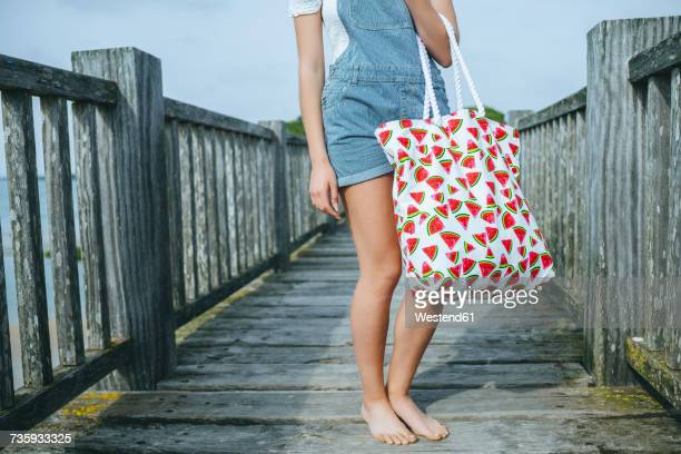 Woman standing on boardwalk holding beach bag, partial view