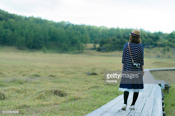 Woman standing on boardwalk in a marshy grassland