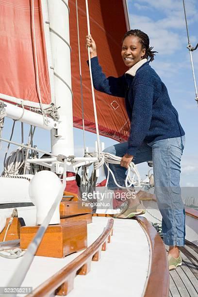 Femme debout en tenant une corde sur le bateau