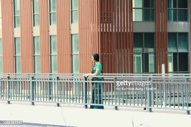 woman standing on bridge against building - ko ko htike aung stock pictures, royalty-free photos & images