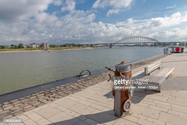 woman standing on bridge over river against cloudy sky,nijmegen,netherlands - nijmegen stock pictures, royalty-free photos & images