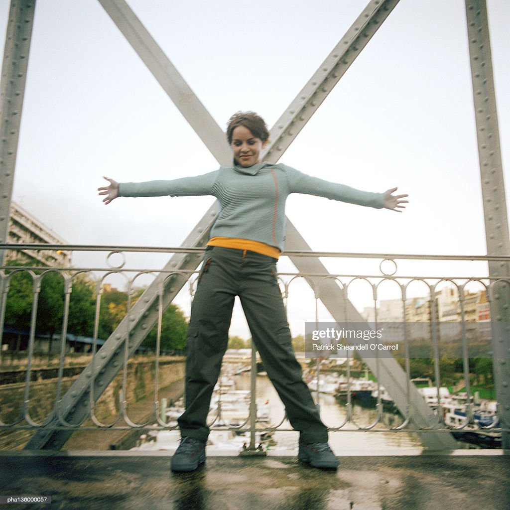 Woman standing on bridge with arms stretched out : Stockfoto