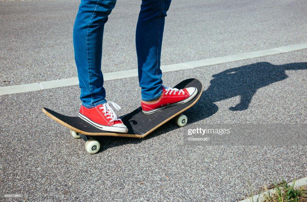 Woman standing on broken skateboard : Stock-Foto