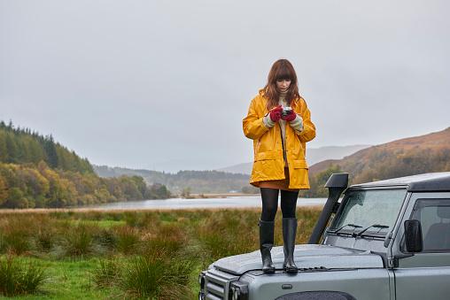 Woman standing on car in beautiful landscape - gettyimageskorea