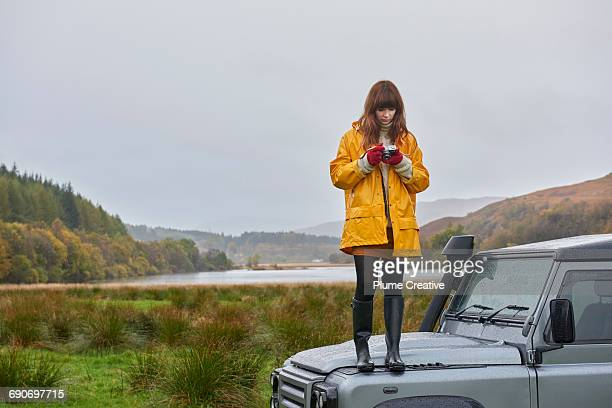 woman standing on car in beautiful landscape - gummistiefel frau stock-fotos und bilder