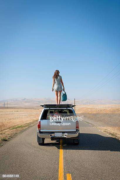 Woman standing on car roof, Highway 1, California, USA