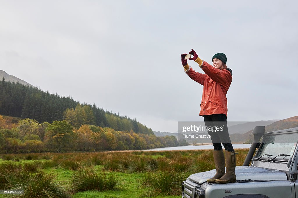 Woman standing on car taking photo : Stock Photo