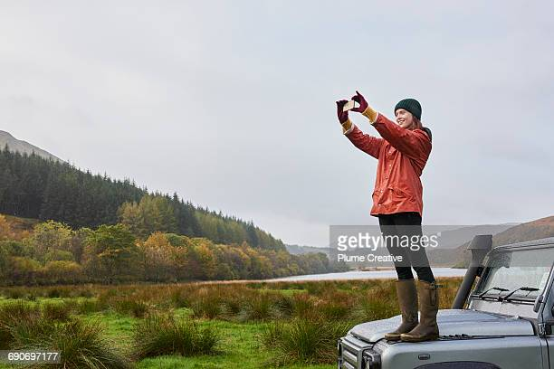 woman standing on car taking photo - photo messaging stock pictures, royalty-free photos & images