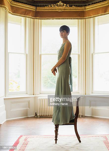 Woman standing on chair in living room