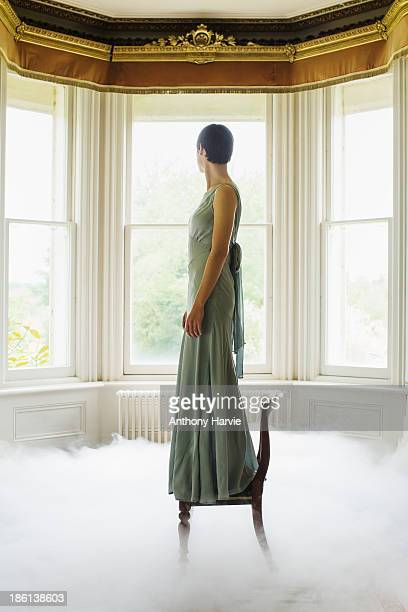 woman standing on chair indoors with misty floor - robe longue photos et images de collection