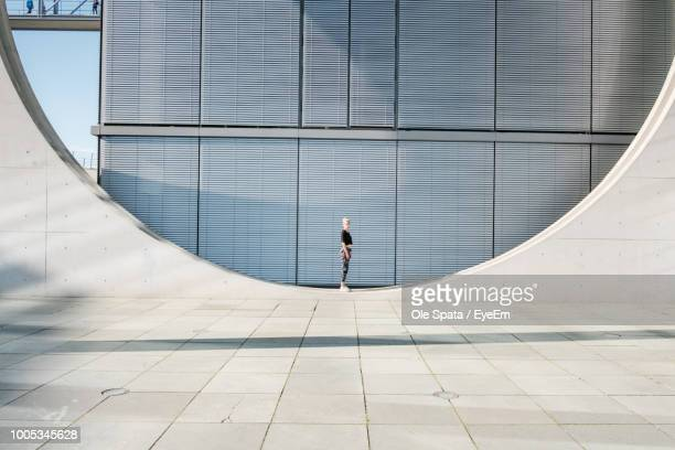 woman standing on circle against building - architecture stock pictures, royalty-free photos & images