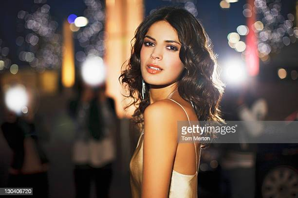 woman standing on city street at night - beroemdheden stockfoto's en -beelden