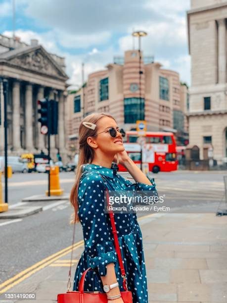 woman standing on city street - dress stock pictures, royalty-free photos & images