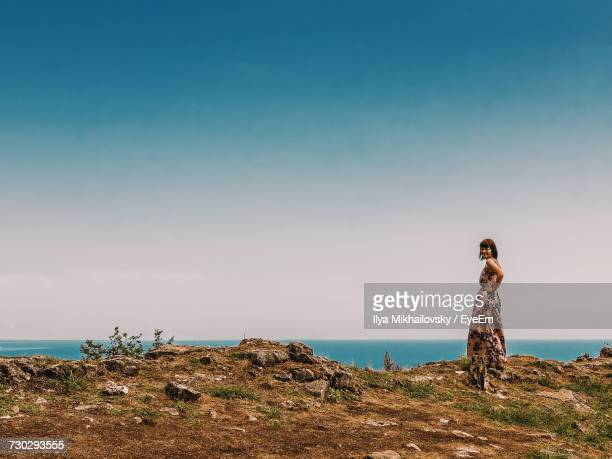 Woman Standing On Cliff By Sea Against Clear Sky