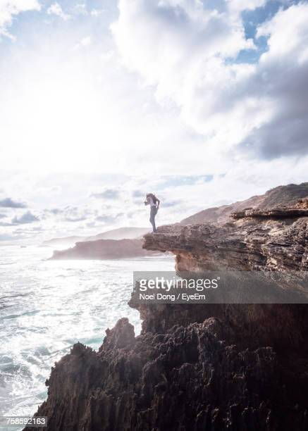 Woman Standing On Cliff By Sea Against Cloudy Sky