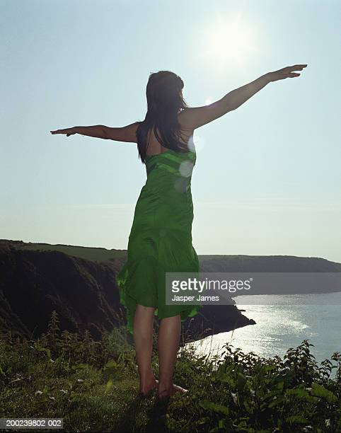 woman standing on cliff edge, arms outstretched, rear view - grünes kleid stock-fotos und bilder