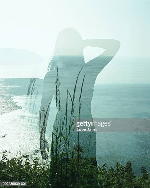 woman standing on cliff edge, rear view (double exposure) - cliff stock pictures, royalty-free photos & images