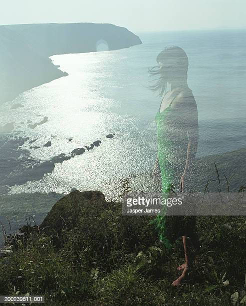 woman standing on cliff edge, side view (double exposure) - green dress stock pictures, royalty-free photos & images