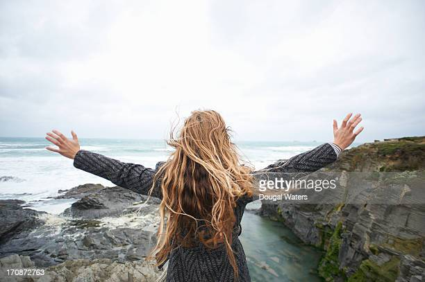 Woman standing on cliff edge with arms stretched.