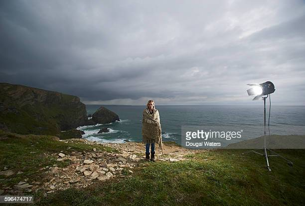 Woman standing on cliff top under movie light.