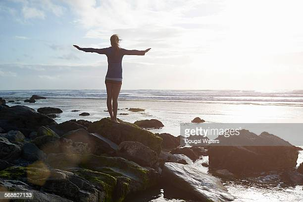 Woman standing on coastal rock with arms stretched