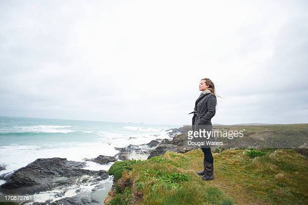 woman standing on coastline with eyes closed. - overcoat stock pictures, royalty-free photos & images