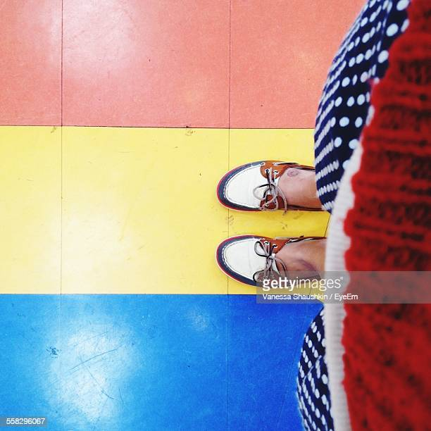 woman standing on colorful floor - multi colored shoe stock pictures, royalty-free photos & images