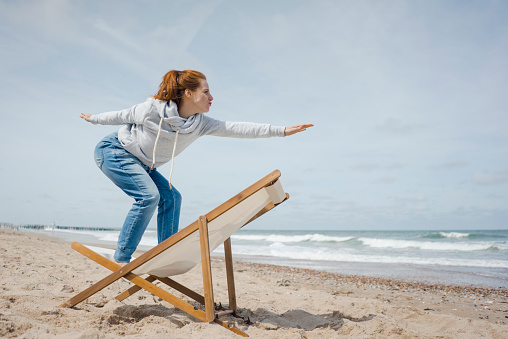 Woman standing on deck chair, pretending to surf - gettyimageskorea