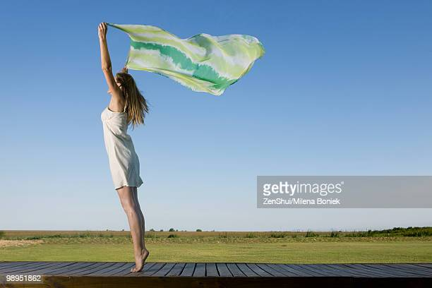 woman standing on deck, holding scarf up in breeze - つま先 ストックフォトと画像