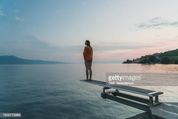 Woman standing on diving board on Geneva lake