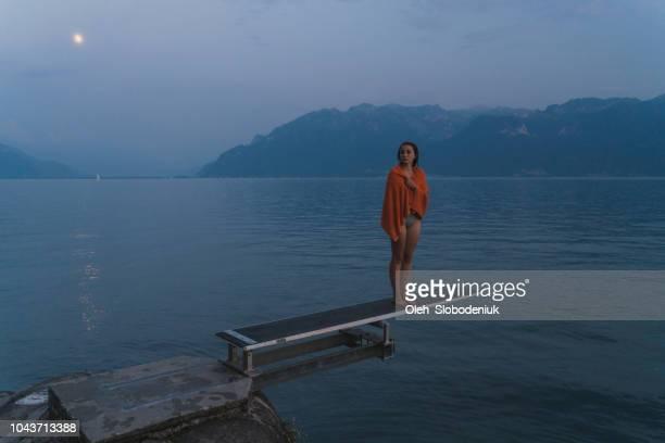 Woman standing on diving board on Geneva lake