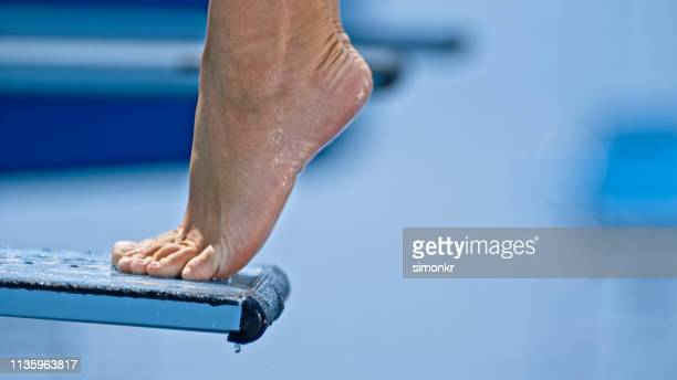 woman standing on diving board - diving board stock pictures, royalty-free photos & images