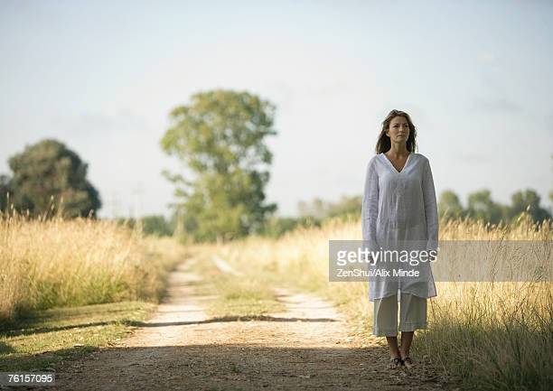 Woman standing on edge of dirt road, next to field