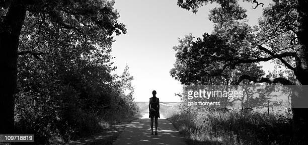 Woman Standing on Edge of Forest Pathway, Black and White