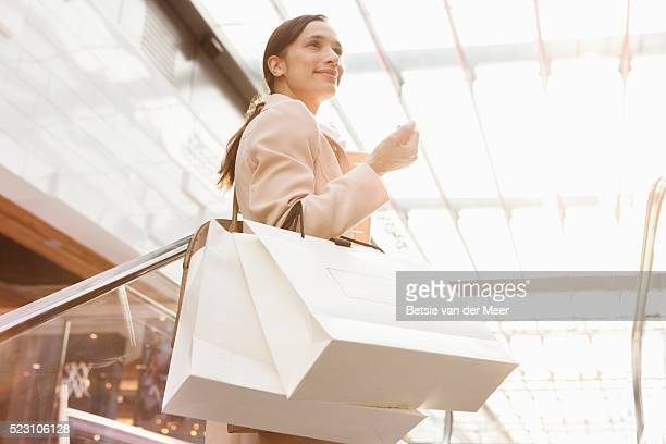 woman standing on escalator holding shopping bags - centro commerciale foto e immagini stock