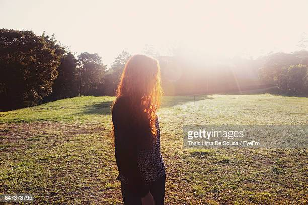 Woman Standing On Field Against Bright Sky