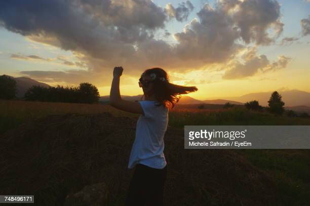 Woman Standing On Field Against Cloudy Sky During Sunset