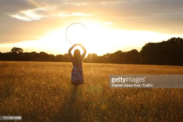woman standing on field against sky during sunset - dawn stock pictures, royalty-free photos & images