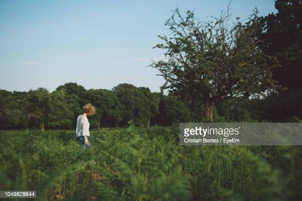 woman standing on field against sky - bortes stockfoto's en -beelden