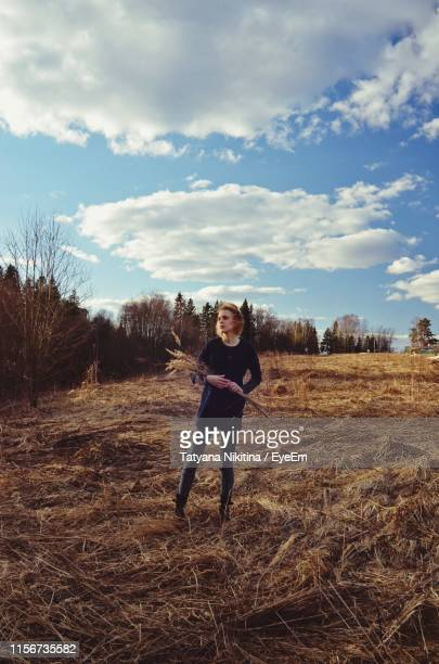 woman standing on field against sky - nikitina stock pictures, royalty-free photos & images