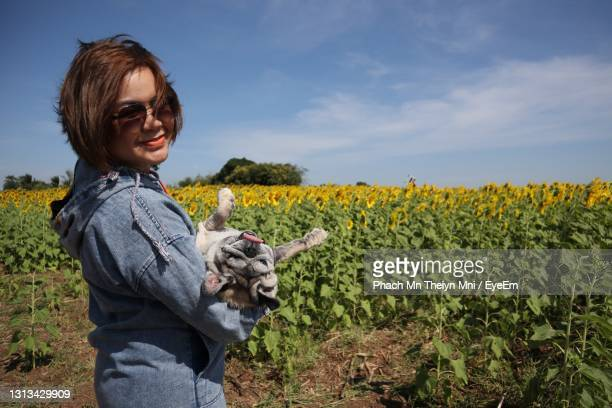 woman standing on field against sky - crucifers stock pictures, royalty-free photos & images
