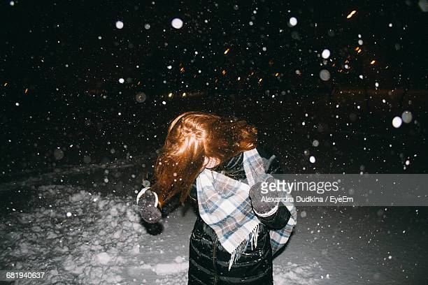 Woman Standing On Field During Snowfall At Night