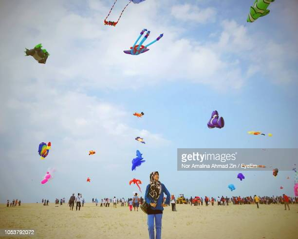 woman standing on field with kites flying against sky - muslim woman beach stock photos and pictures
