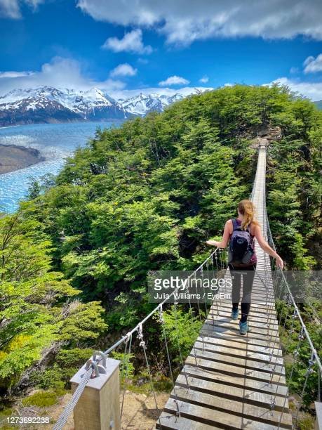woman standing on footbridge against mountain - chile stock pictures, royalty-free photos & images