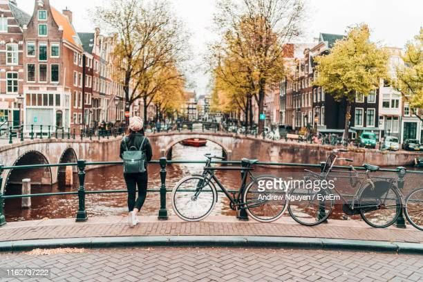 woman standing on footbridge over canal in city - amsterdam stock pictures, royalty-free photos & images