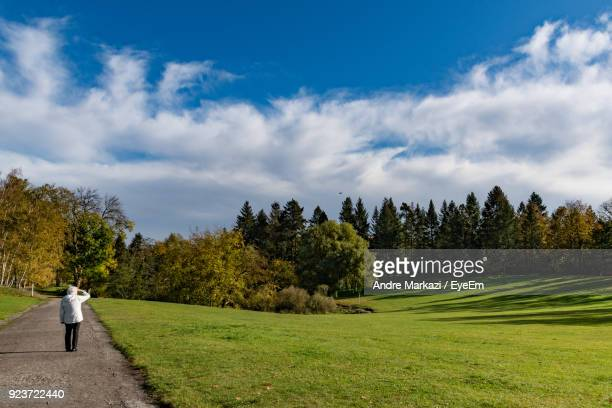 Woman Standing On Footpath By Field Against Clear Sky