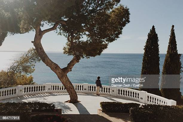 Woman Standing On Footpath While Looking At Sea
