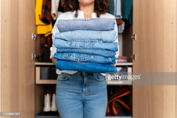 woman standing on front of wardrobe holding stack of blue jeans - sistemazione foto e immagini stock