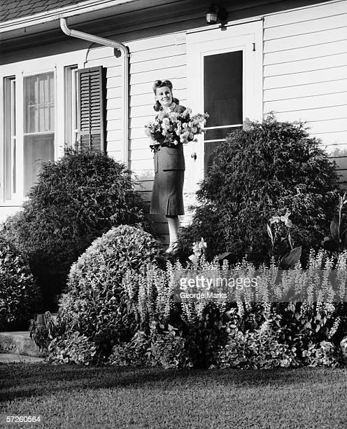 Mulher de pé na frente varanda de casa segurando ramo de flores,