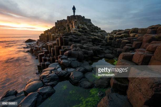 Woman standing on Giants Causeway at sunset, County antrim, Northern Ireland, UK